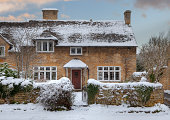 Pretty Cotswold cottage in snow, Broadway, Worcestershire, England.