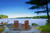 Two Muskoka chairs sitting on a rock formation in cottage country. The chairs are facing a calm lake in early morning.
