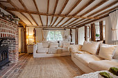 16th Century English cottage living room with cast iron fire beutifully decorated in pastel colours and furnishings with expose brick floor, expose brick chimney breast, beams and timbers, matching ch