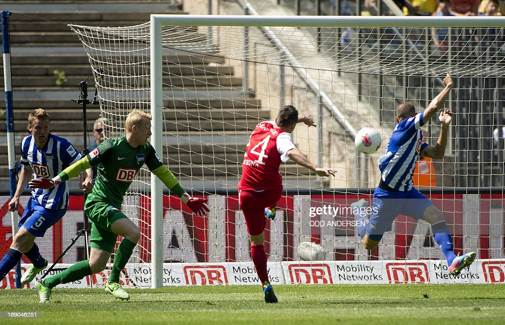 Cottbus' French midfielder Nicolas Farina (C) scores past Hertha Berlin's goalkeeper Sascha Burchert (L) during the German second division Bundesliga football match Hertha Berlin vs Energie Cottbus at the Olympic stadium in Berlin on May 19, 2013. Hertha Berlin has won the 2012-13 second division and secured promotion to the first division Bundesliga the year after they got relegated after loosing in the play offs. AFP PHOTO / ODD ANDERSEN