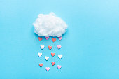 Cotton Ball Cloud Rain Sugar Candy Sprinkle Hearts Red Pink White on Blue Sky Background. Applique Art Composition Kids Style. Valentines Love Charity Concept. Greeting Card Poster