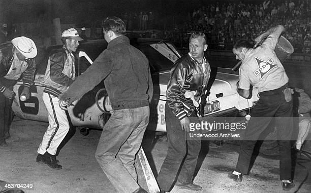 Cotton Owens facing camera ace race mechanic for the Carolina Dealers hustles hard during a night race when driver David Pearson makes a pit stop...