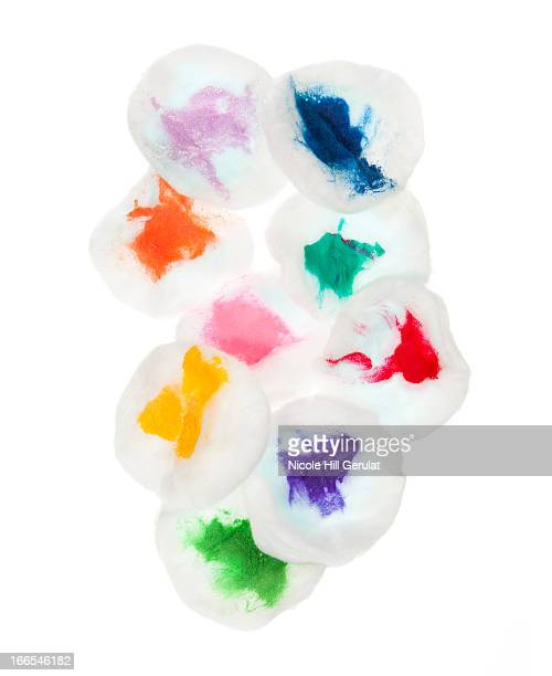 Cotton pads stained with colorful paint on white background