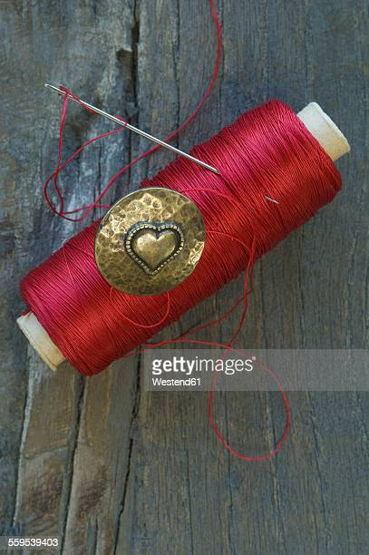 Cotton reel, sewing needle and metal button with heart