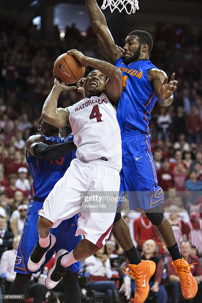 Coty Clarke #4 of the Arkansas Razorbacks drives under the basket against <a gi-track='captionPersonalityLinkClicked' href=/galleries/search?phrase=Patric+Young&family=editorial&specificpeople=7405616 ng-click='$event.stopPropagation()'>Patric Young</a> #4 of the Florida Gators at Bud Walton Arena on January 11, 2014 in Fayetteville, Arkansas. The Gators defeated the Razorbacks 84-82.
