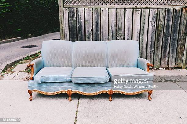 Couch Against Wooden Fence On Street