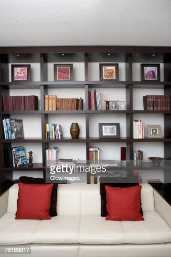 Couch in front of shelves in a living room : Foto de stock