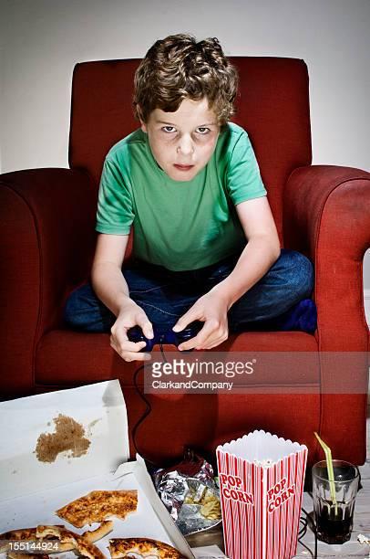 Couch-Potato junge umgeben von Junk Food spielen Computer-Spielen