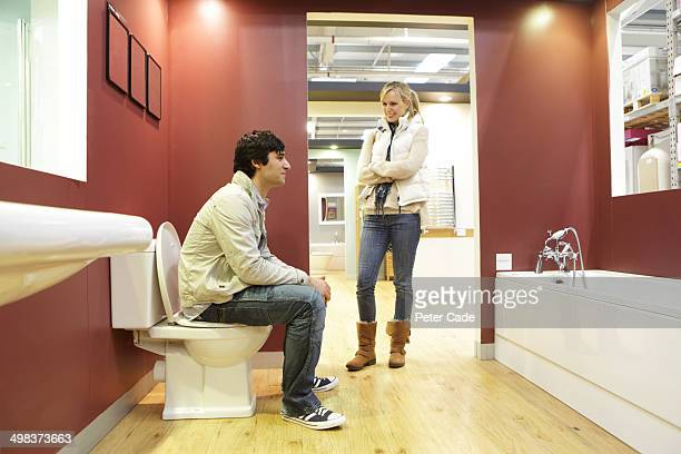 Coule in bathroom showroom, man sat on toilet