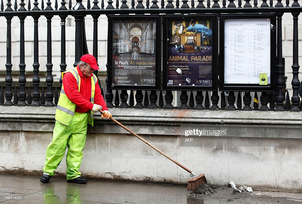 A council cleaner sweeps dirt and debris from the pavement outside St Paul's Cathedral in central London, on February 28, 2012, following the eviction of protesters from the Occupy camp outside the Cathedral in the early hours of Tuesday. Police dismantled the anti-capitalist camp outside London's St Paul's Cathedral early Tuesday, arresting 20 people as they brought a swift end to the last major Occupy protest around the world. AFP PHOTO/JUSTIN TALLIS