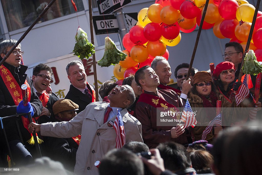 Council Member Robert Jackson, center, pretends to eat lettuce, which is part of the traditional custom of the lion dance, during the 14th Annual Chinatown Lunar New Year parade on February 17, 2013 in New York City. This year celebrates the Year of the Snake.