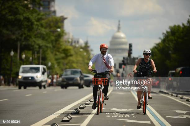 DC council members Elissa Silverman right and Charles Allen demonstrate the usage of the dock less bike system Mobike in Washington DC September 15...