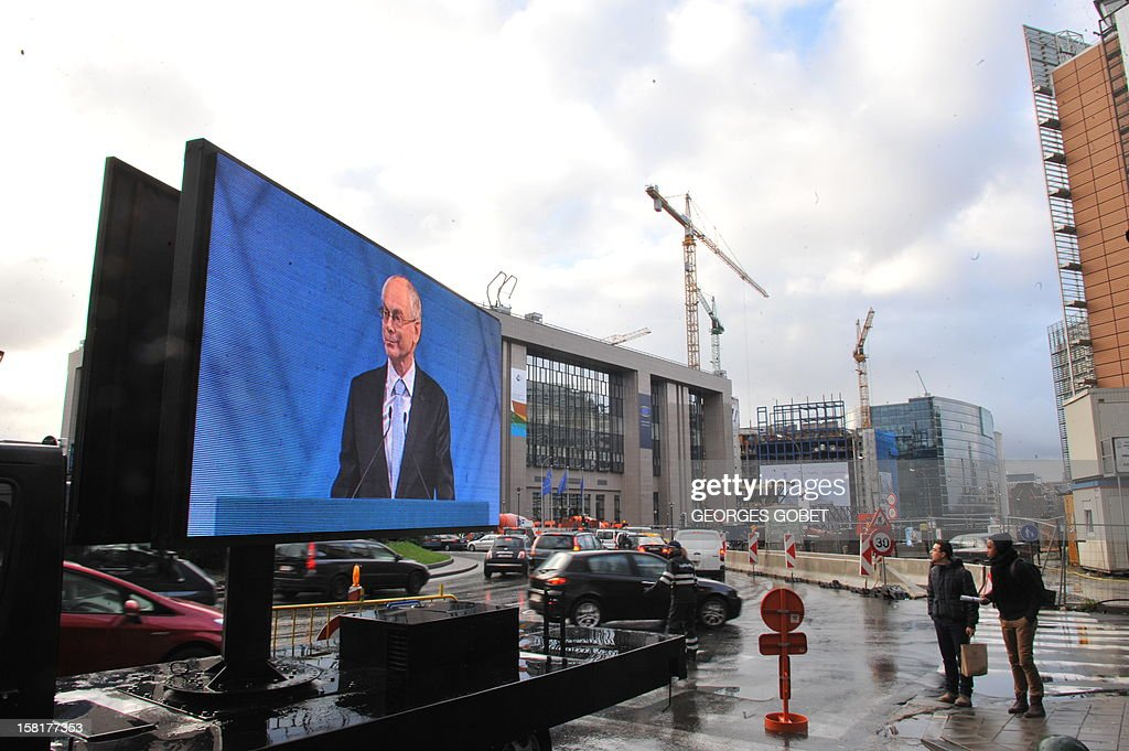 EU Council president Herman Van Rompuy appears on a giant screen in front of the European Council during the broadcast of a ceremony for the Nobel peace Prize to European union on December 10, 2012 at the EU Headquarters in Brussels. AFP PHOTO GEORGES GOBET