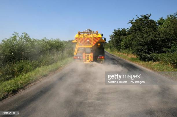 A council road gritter spreads sand on a heatdamaged road at Kirkby Thore in Cumbria in a bid to prevent the road melting in the sweltering conditions