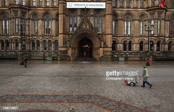 A council road sweeper walks across Albert Square in front of Manchester City Town Hall as the authority announces it may have to shed up to 2000...