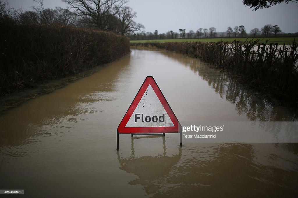 A council sign sits in flood water on a road near Lingfield on December 27, 2013 in England. High winds and flooding are continuing to cause problems in parts of southern England. Some homes are still without power.