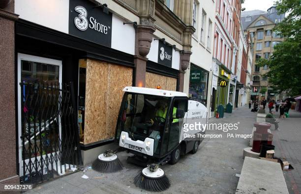 A council worker cleans up debris on St Ann's Square in Manchester after rioting in the city centre last night