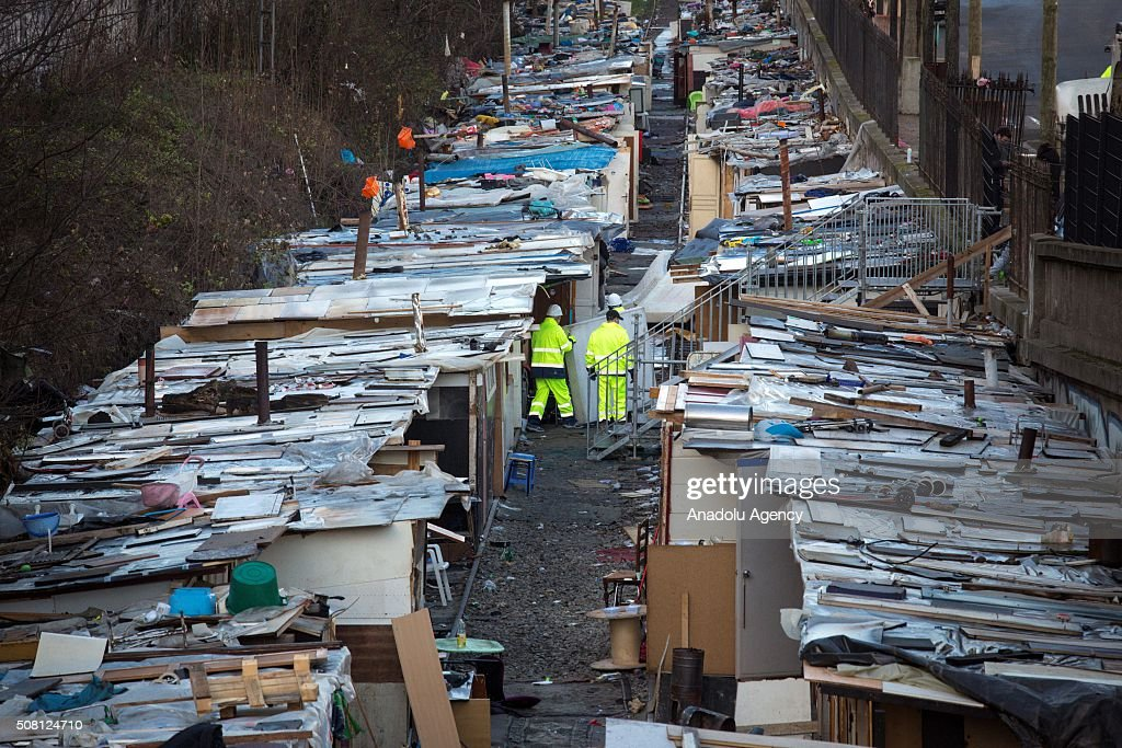 Council workers clearing up the camp after the evacuation by Gendarmes of a Roma refugees' camp deemed insecure and unsanitary on former railway...