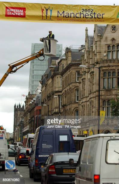 Council workers in Manchester erect a banner in the city centre welcoming visitors to the Commonwealth games which start in the city on Thursday *The...