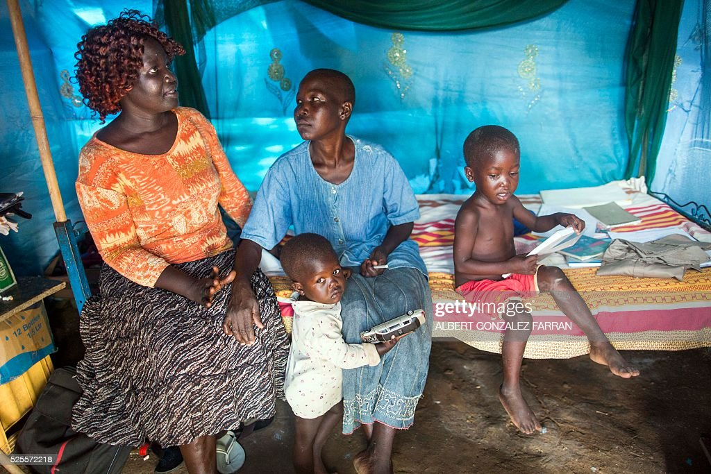 HIV counsellor Angelina Dwoki (L) interacts with one of her patients, Rose Koluwa (R), an HIV positive mother of six boys and one girl, in her shelter in Juba on April 28, 2016. Rose was infected by her husband, who died a bit later. Since then, she lost her job and temporarily quit taking anti-retrovirals because she thought they were not helping her. . South Sudan experiences a generalised HIV epidemic, with concentration of high prevalence in urban areas, basically in the Equatorial region. According to UN AIDS, nearly 3% of the adult population is HIV positive, with 13,000 deaths every year and 18,000 new infections annually. However, these figures should be likely higher if there was a more accurate evaluation among the rural population. / AFP / Albert Gonzalez Farran