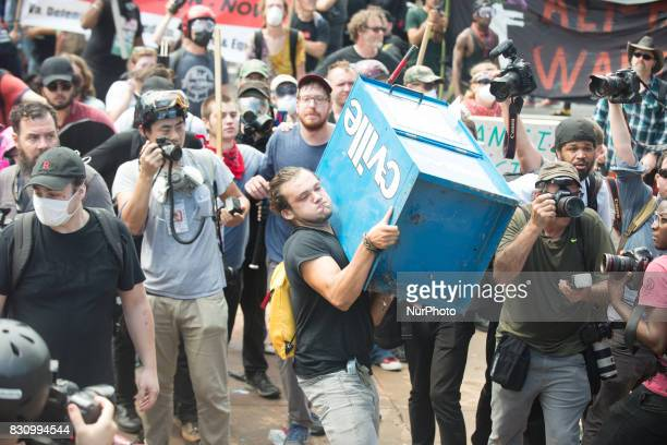 A counter protester prepares to throw a newspaper box at white supremacists in Emancipation Park in Charlottesville Virginia on August 12 2017