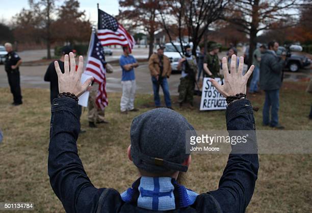 A counterdemonstrator prays in front of armed members of the socalled Bureau of AmericanIslamic Relations protesting at the Islamic Association of...