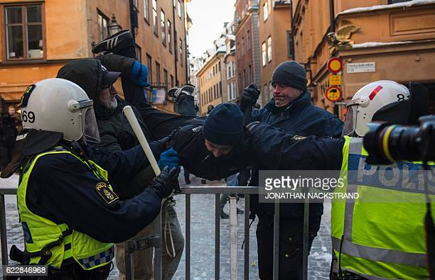A counterprotester is arrested by the police as they keep them away from the Nordic Resistance Movement's during a demonstration in central Stockholm...