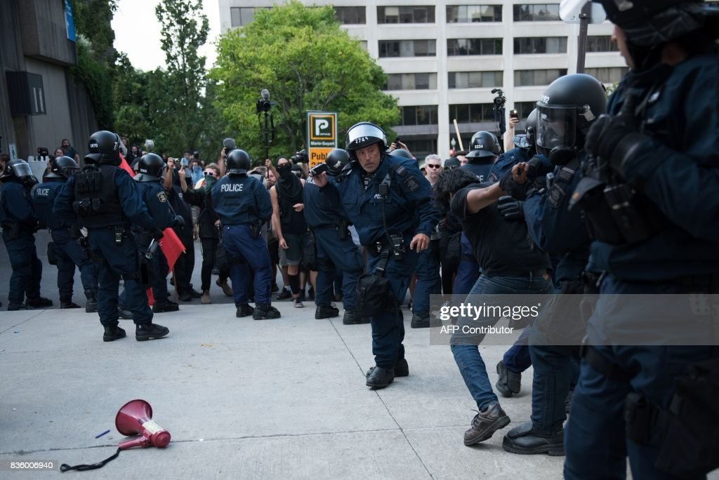 Counter-protesters clash with police in Quebec City, Canada, on August 21, 2017. Clashes erupted Sunday between police and dozens of anti-racist activists on the sidelines of a pro-immigration rally in Quebec City while a demonstration organized by extreme-right activists gained little traction. In a bid to keep the two rallies apart, police erected a security cordon but declared the anti-racist demonstration illegal after sporadic clashes broke out and hooded individuals threw projectiles at police. PHOTO / Alice Chiche