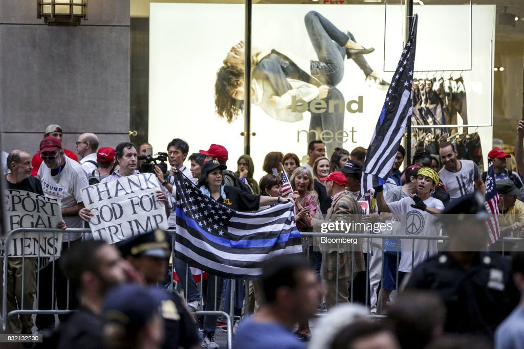 Counter-protesters hold American flags and signs during the 'Defend DACA & TPS' rally outside of Trump Tower in New York, U.S., on Tuesday, Aug. 15, 2017. A day after belatedly faulting white supremacists for deadly clashes in Virginia, President Donald Trump returned to his controversial position that there was 'blame on both sides' for the weekend violence, saying that liberal counter-protesters also bore responsibility. Photographer: Jeenah Moon/Bloomberg via Getty Images