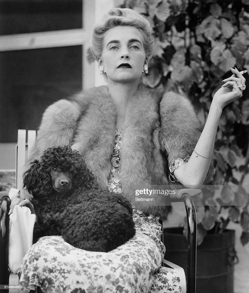 Countess Haugwitz-Reventlow (<a gi-track='captionPersonalityLinkClicked' href=/galleries/search?phrase=Barbara+Hutton&family=editorial&specificpeople=930426 ng-click='$event.stopPropagation()'>Barbara Hutton</a>) is seated with a poodle in her lap as she watches a tennis match at Palm Beach, Florida, January 18, 1940.