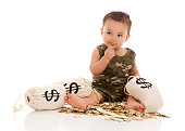 Adorable mixed race baby boy playing with plastic gold coins and money bags.  One gold coin in his mouth.  Isolated on white.