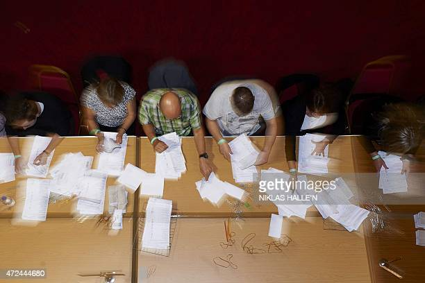 Counting staff sort ballot papers at a vote counting centre in Margate southeast England on May 7 2015 during the UK general election Prime Minister...