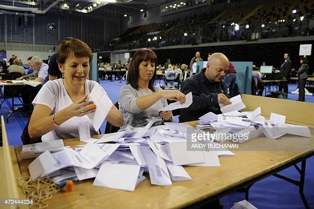 Counting staff sort through ballot papers at the counting centre at the Emirates Arena in Glasgow on May 7 2015 after the polls closed in the British...
