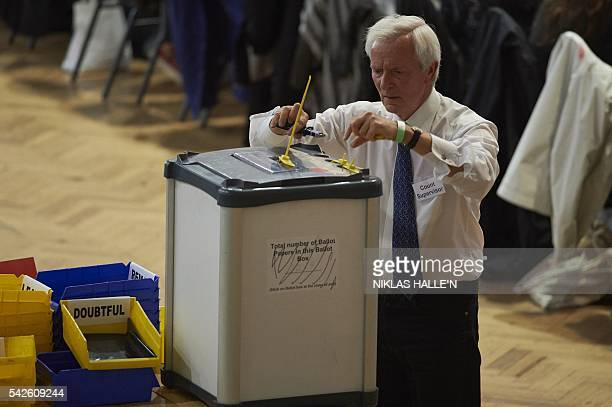 A counting supervisor opens a ballot box at a vote counting centre at The Royal Horticultural Halls in central London on June 23 2016 Voting has...
