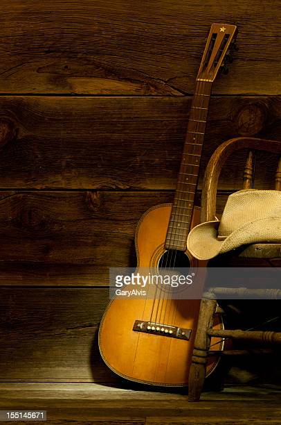 Country and Western scene w/ guitar,chair,cowboy hat-barnwood background