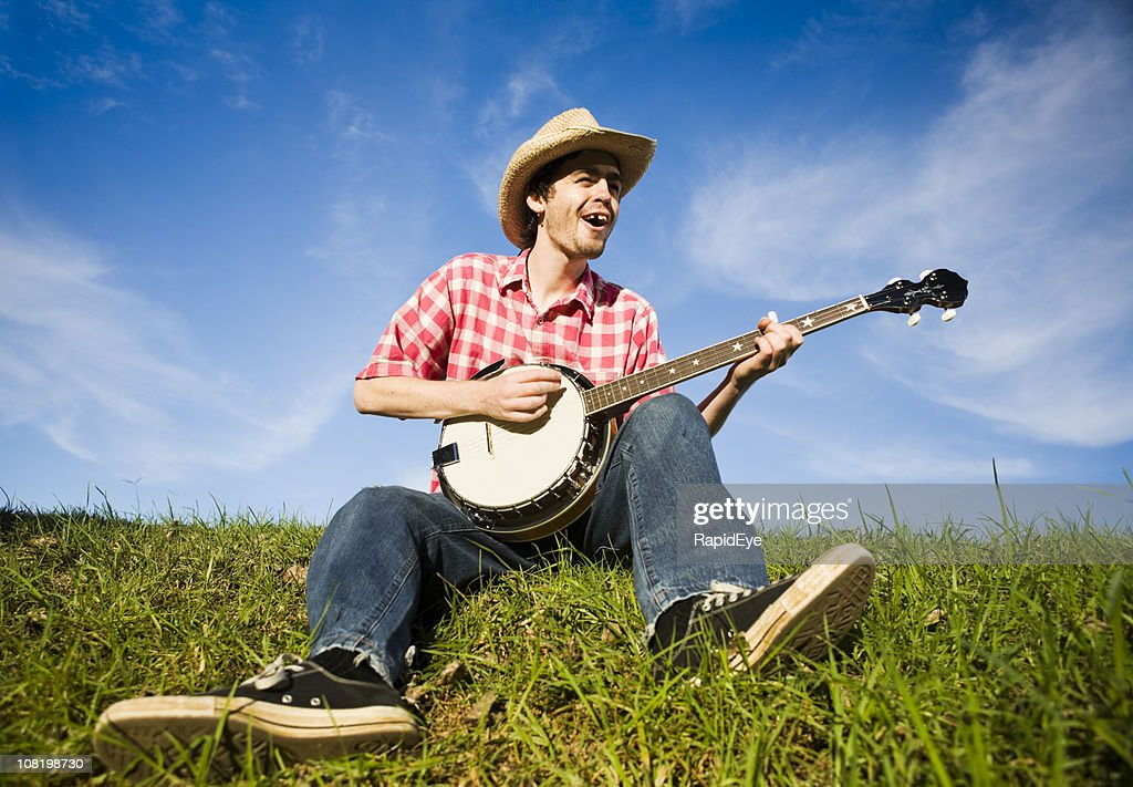 Country boy plays the banjo in a rural summer meadow