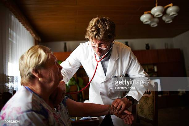 Country doctor Dieter Baermann measures the blood pressure of an elderly patient Giesela Herfert in the patient's home on August 8 2011 in...