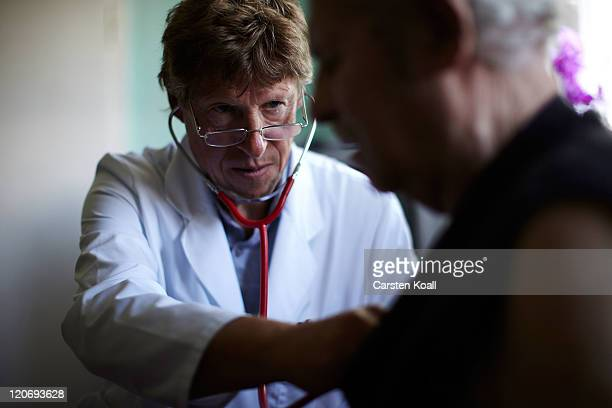 Country doctor Dieter Baermann measures the blood pressure of an elderly patient Wilhelm Schilke in the patient's home on August 8 2011 in...