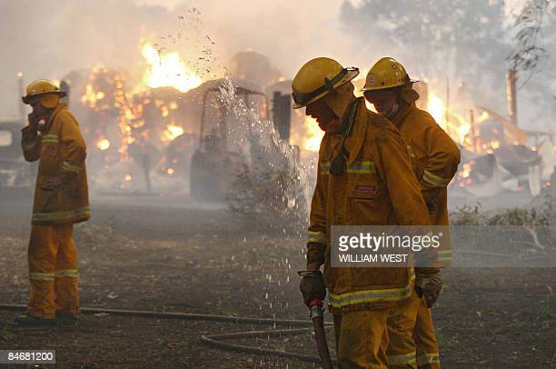 Country Fire Authority volunteers pack away their hose as a barn burns in the background after they managed to save the house close to Labertouche...