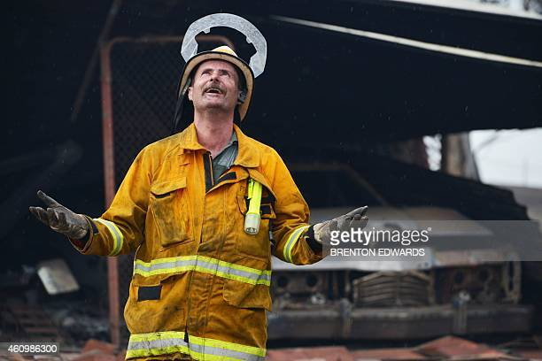 A Country Fire Service volunteer reacts as rain starts to fall near One Tree Hill in the Adelaide Hills northeast of Adelaide on January 3 2015...
