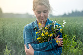 Country Girl Holding Meadow flowers, wind swept hair in the breezy summer time.
