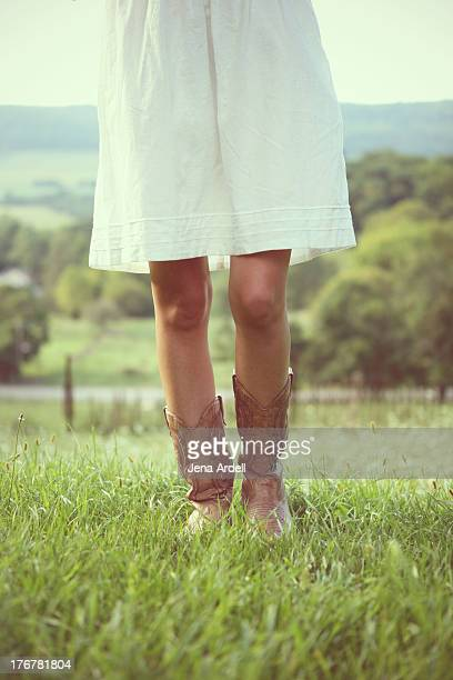 Country girl wearing cowboy boots and white dress