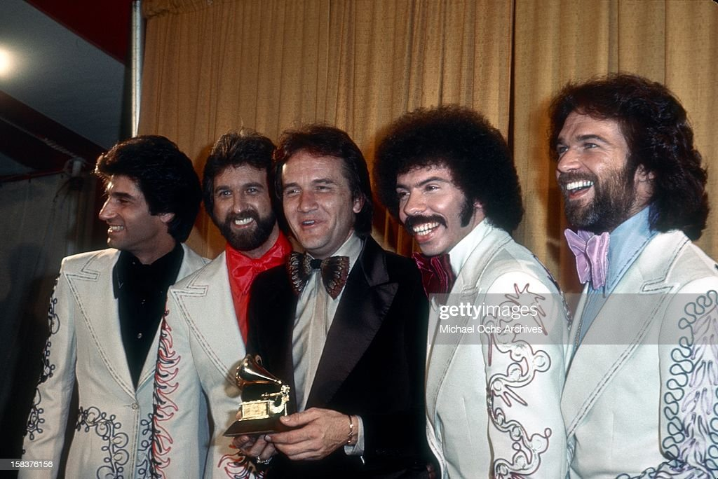 Country group the Oak Ridge Boys poses for a portrait with country singer Roger Miller as he holds a Grammy backstage at the Grammys which were held...