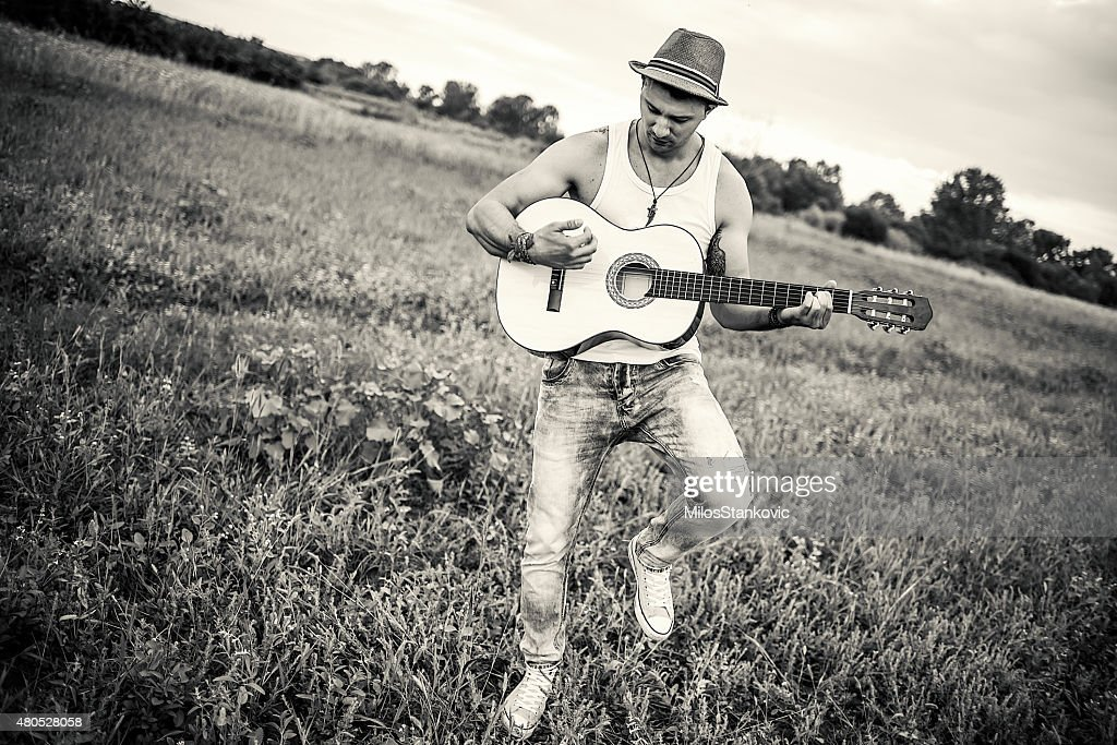 Country guitarist playing the guitar in field : Stock Photo