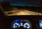A curving country road in Utah, USA, illuminated by a car's headlights, with the car's dashboard in the foreground.