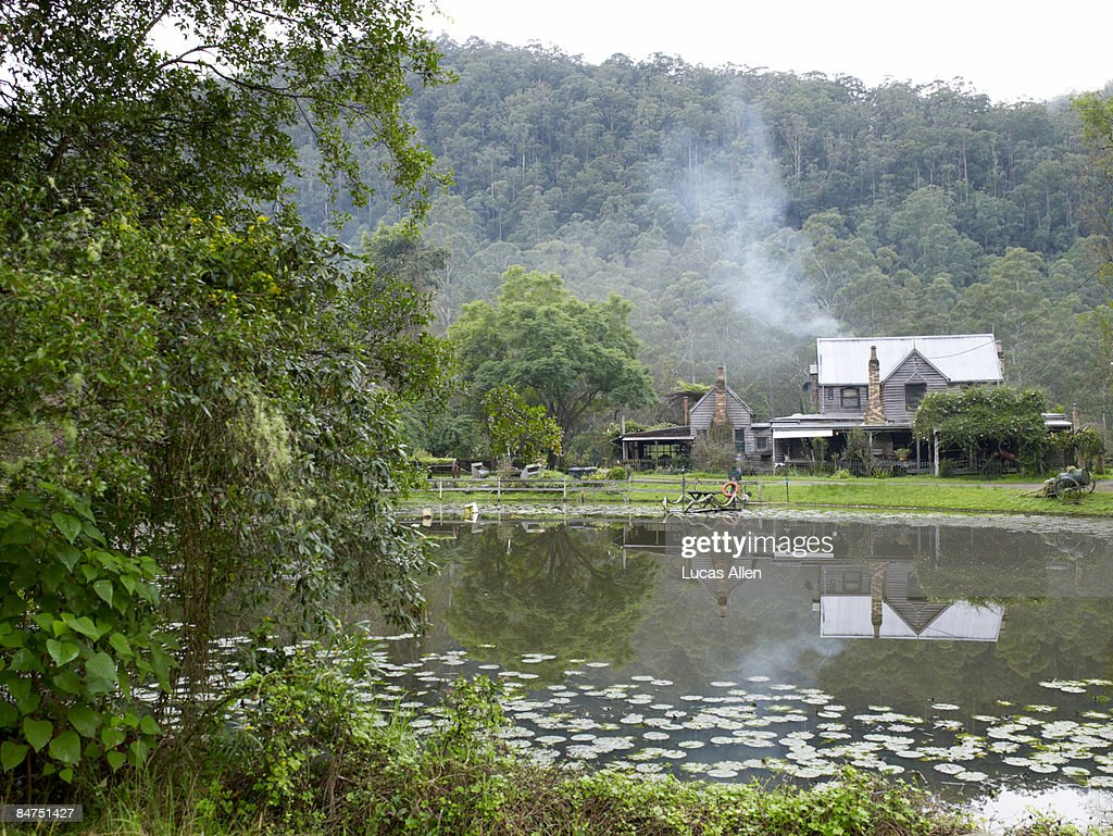Country home on a pond with smoking chimney : Stock Photo