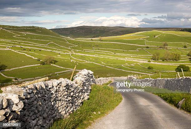 Country lane and dry stonewalls Malham Yorkshire Dales national park England UK