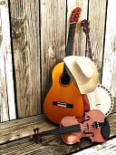 Country music background with stringed instruments. Guitar, banjo , violin and a cowboy hat leaning against a wood fence. Room for text or copy space.