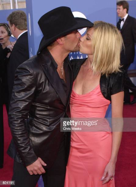 Country music singer Tim McGraw gives a loving kiss to wife Faith Hill February 21 2001 outside the 43rd Annual Grammy Awards at the Staples Center...