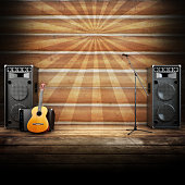 microphone, guitar and speakers with wood flooring and sunburst background. Advertising concept with room for text or copy space.Photo realistic 3d model scene.